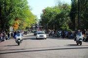 The annual Maple Leaf Festival parade is led by a Baldwin City Police Department car as the parade heads west down High Street before turning at Sixth Street and heading north.