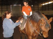 Trainer Shaughnessy Morris helps Katie Fulkerson with her saddle Saturday at Justindeavor Stables in Kansas City, Kan.