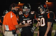 Bonner Springs football coach Lucas Aslin instructs his defense during a break in the action. The Braves&#39; defense struggled in a 76-40 loss to Gardner-Edgerton in the Class 5A state playoffs.