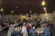 Senior citizens and their families gather for a Thanksgiving meal at the Basehor VFW Post on Saturday, Nov. 19. Post officials estimated that about 200 people came through during the afternoon meal, for which volunteers prepared eight turkeys, two hams and 15 pumpkin pies.