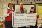 Basehor Elementary School principal Teri Boyd (left) and Basehor-Linwood Superintendent David Howard award a grant check to first-grade teacher Cynthia Fletcher from the Basehor-Linwood Education Foundation on Monday.