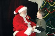 Four-year-old Bryce Orlich of Kansas City, Kan., chats it up with Santa Claus during the Holiday at Grinter event.