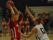 Tonganoxie's Colby Yates looks past the outstretched arms of Mill Valley's Staton Rebeck. Rebeck and the Jaguars beat THS, 77-65.