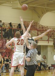 Tonganoxie's Dane Erickson battles Turner's Eric Dougherty for the opening tip on Tuesday.