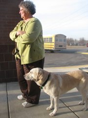 Zip, an 8-year-old yellow Labrador, stands beside Marilyn McGown as they watch students ride away on buses outside Glenwood Ridge Elementary School south of Basehor. McGown began using social dogs trained by KSDS in 1994, a year after becoming a school counselor.