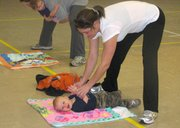 "Jana Deters of Basehor bends down and helps her son Colton, 9 months old, clap his hands during the ""non-walkers"" portion of a Basehor Parents as Teachers fitness class Friday morning at Basehor Elementary School. Deters said she enjoyed learning ways to include her son while working out, and she said Colton had a good time, as well."