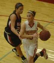 Tonganoxie's Hannah Kemp drives to the basket while Bishop Ward's Caitlin Reed plays defense.