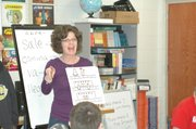 Susan Swabb holds up a storyboard the class created for their story about a spider and a chicken looking for ice cream.
