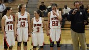 Shawnee Mission Northwest seniors Jessica Johnson, Katie Biggers, Mary Slattery and Sarah Schmidt receive the sub-state trophy after defeating SM West, 53-49, in overtime Friday. The Cougars came back from a 12-point fourth-quarter deficit and, after going 14-49 the last three seasons, are now headed to state at 16-6.