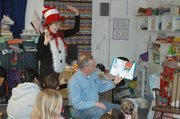 Judy Miksh, left, dressed as The Cat in The Hat, pantomimes her character&#39;s actions as Merle Parks reads the book of the same name to Head Start students Friday.