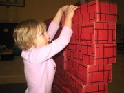 Katherine Whiteaker, 5, of Basehor stacks a cardboard brick atop the wall she was constructing. After it was complete, she and her brother Joshua, 3, knocked it down.