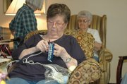 Carolyn Essey tries her hand at the Knifty Knitter to make a baby-sized stocking cap at Nettleton Manor on Monday. The new Missions for Newborns group at the senior apartments is meeting at 10 a.m. on Mondays and is not limited to residents of the apartments.