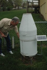 Gil Hoag bends to open the electronic rain gauge, powered by a solar panel, given to him by the National Weather Service. The gauge records daily readings onto a chip, which Hoag then sends to the NWS each month. Also in his backyard, Hoag checks another rain gauge daily and an electric temperature gauge that tracks the highs and lows.