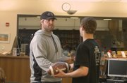 Ryan Lilja, offensive lineman for the Kansas City Chiefs, hands an autographed football to Shawnee Mission Northwest wrestler Colton Amos Wednesday for raising $1,022 for the Down Syndrome Guild of Greater Kansas City. Lilja visited the school to congratulate the SM Northwest wrestling team for its efforts in raising more than $1,800 for the organization through First Downs for Down, a Kansas City-based charity organization that partners with the Chiefs to raise money for Down Syndrome research and organizations.