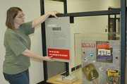 """Michelle Wolfe of the Mid-America Arts Alliance straightens the display at one of the exhibit's stations about images used on """"campaign"""" materials in the civil rights movement. The M-AAA set up the exhibit at the Wyandotte County Historical Museum Monday."""