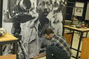 "Jeremie Hoffmann, of the Mid-America Arts Alliance, straightens an image of Gordan Parks, a Kansas native and well-known photographer, one of the chief displays of the ""For All the World to See."" The exhibit, on display at the Wyandotte County History Museum beginning Monday, examines images of blacks in the media and popular culture during the civil rights movement."