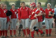 Amanda Holroyd, front, is met by her teammates after hitting a solo home run.