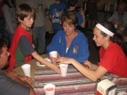 "Basehor Intermediate School fifth-grader Jake Ulreich serves drinks to Amy Donnelly of Basehor and her daughter Jenna, an eighth-grader at Basehor-Linwood Middle School, at the Basehor VFW Post on Friday, April 13. Donnelly's son Dylan, also in fifth grade at BIS, was also helping serve diners during the post's spaghetti fundraiser for BIS fifth-graders' Wreaths Across America projects. Dylan comes regularly to the post's twice-a-month breakfasts, Amy said. ""He loves to come down here,"" she said."