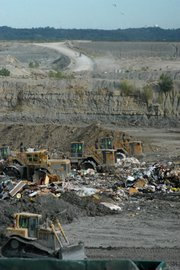 As trucks dump load after load of garbage and debris into the active cell at the landfill, a corps of heavy machine operators work continuously to level and bury the trash.