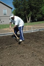 Bryan Schoonover hoes a row into the plot he and his mother share at the community garden. Though they have never gardened before, they say they hope to realize some savings by growing their own vegetables.