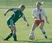 Basehor-Linwood's Alyssa Harwick battles Tonganoxie's Kelsi Briggs for the ball.
