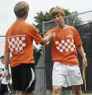 Spencer Bush and Quinton Schneck slap fives between sets against Wichita Collegiate in the second round of the 4A state tennis tournament on May 11 in Topeka.