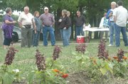 Visitors munch snacks and sip drinks at the grand-opening event for the Basehor Community Garden on May 12.
