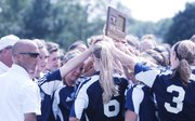 The Mill Valley girls soccer team and coaching staff gather around its 5A state runners up trophy following Saturday's 4-1 loss against St. Thomas Aquinas.