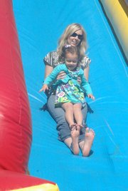 Diana Diale of Basehor slides down an inflatable slide with her 3-year-old daughter Emerson at the 2012 Basehor Dairy Days festival in Basehor City Park on June 2.