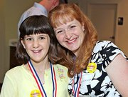 Michelle Schmidt, right, gives a hug top Grace Altenhofen, who nominated Schmidt for a Kindest Kansas Citian award.