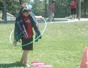 "Luke Jennings, 10, swings a hula hoop while wearing beach attire at Basehor United Methodist Church's Vacation Bible School on Tuesday. In this relay competition at the VBS's games station, competitors had to put on a beach costume, swing the hula hoop, then take the costume off as fast as they could. The theme of the weeklong event is ""Operation Overboard."""