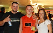 Tyler Holland, center, poses with his stepfather, Greg Harris, and mother, Jackie Harris after his first sanctioned fight in February in Shawnee.