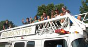 Members of the state champion Basehor-Linwood High School basketball team, along with coach Mike McBride, ride by during the Basehor Fourth of July parade.