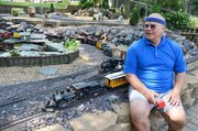 Shawnee City Council Jim Neighbor has blended garden features like dwarf trees, flowers and a pond with lily pads into his backyard railroad.