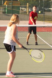 Aaron Lewis, right, lobs a ball to a participant in his free summer tennis camp.