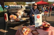 Clara Richardson waits for the next apple-seeking customer at the Lawrence Farmers Market on a busy Saturday.
