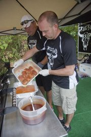 Truebud BBQ pitmaster Tim Grant, Tonganoxie, with help from Boyd Abts of Eudora, prepares chicken for the judges during the Smokin' on Oak barbecue competition Aug. 25, 2012, in Bonner Springs. Truebud is one of the top barbecue teams in the country right now, hanging in the top 10 of the Kansas City Barbeque Society's Team of the Year points chase.