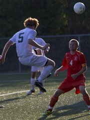 Free State junior Alex Trent (5) uses his head to slip the ball past Bonner Springs&#39; Austin Schuler (4) and into the goal for a score during their soccer match Thursday, August 30, 2012, at FSHS.