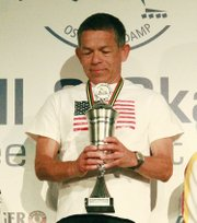 Hernan Diaz of Shawnee holds the trophy he received for winning the inline skating competition in his age group at the World Masters Championship recently in Germany.