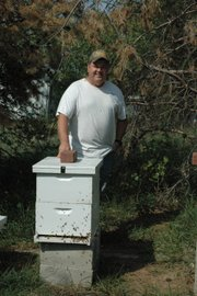 Walt Stephen stands near one of about 10 bee colonies on his property in Bonner Springs; he has 40 overall, the others located on farms in Leavenworth and Douglas counties. What started out as a method to pollonize his apple trees turned into a lucrative side business and has earned Stephen and his wife first-place ribbons for the best honey products at the Kansas State Fair.