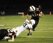 MVHS senior Jake Theis (21) brings down Bonner Springs quarterback Jordan Jackson.