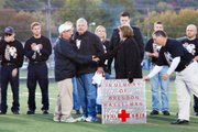 BLHS coach Steve Hopkins greets Linda and Lewis Kasselman before Friday's game at Bonner Springs. A moment of silence was held for Brendon Kasselman, who passed away earlier this year after a battle with cancer. More than $5,000 was raised for a scholarship fund in his name, and both teams gathered to remember Kasselman with friends and family on the field at David Jaynes Stadium.