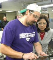 U.S. Secretary of Labor Hilda Solis got a close up look at the workings of a metal lathe operated by student Aaron Mills of Bonner Springs during the Secretarys visit to KCKCCs Technical Education Centers Thursday. 