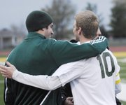 BLHS coach Austin Knipp and senior Lane Young embrace after Young stepped off the field upon taking the first kick. Assistant coach Jeff Stromme also joined in congratulating Young.