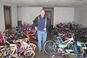 Neil Holman, Shawnee parks and recreation director, is surrounded by children's bicycles to be recycled and distributed through a program that benefits the needy and promotes cycling among younger generations.