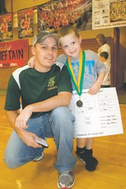James Gallet, left, shown here with his son, Caden, started the Bobcat Wrestling Club, a youth club in Basehor that expects to see its numbers increase to 80 this season.