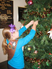 Brooklyn Ziebell, one of the Brownies with Bluejacket-Flint Troop 500 who volunteered to decorate City Hall for the holidays, hangs an ornament.