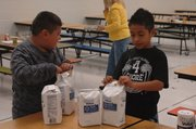 David Ramirez (left) and Adrian Jimenez open bags of sugar as they help set up the pie making stations.