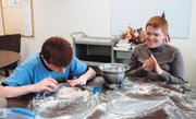 Dylan Baker, left, a seventh-grader in Shawnee Mission North's communication and behavioral disorders program, and 10th-grader Lucas Hart, also in the program, shape the dog biscuit dough during a recent baking session.
