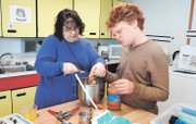 With the help of teacher Judith White, left, eighth-grader Reed Hosley scoops peanut butter into a mixing bowl.